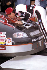 Picture of Dale leaning over and kissing the hood of his car.